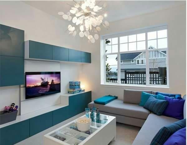 Turquesa oscuro en el mueble de la TV, blanco en las paredes y gris en el sofá.
