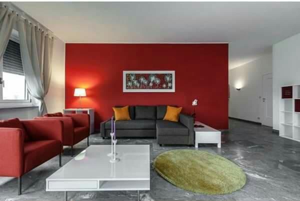 Rojo en paredes y sillones gris en el suelo y sofá, el resto en blanco.