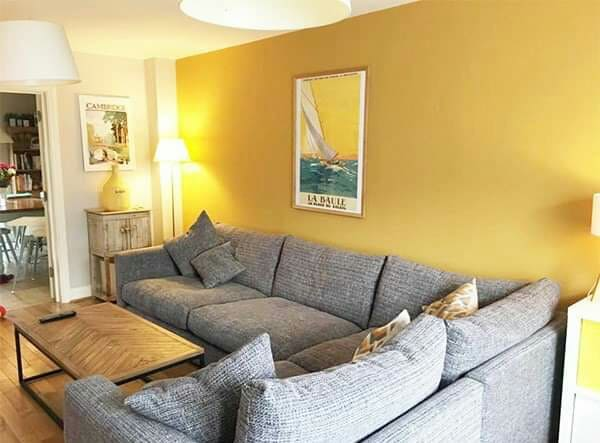 Colores mostaza, color tierra en el resto de las paredes, gris medio en el sofá, madera en suelos y mesa
