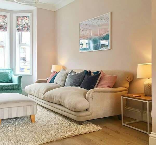 Colores rosa soft en paredes, sofá en beige, sillón azul y madera en el suelo.